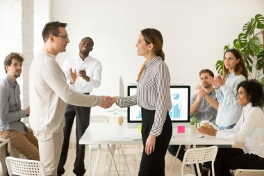 Female boss promoting rewarding handshaking male employee while