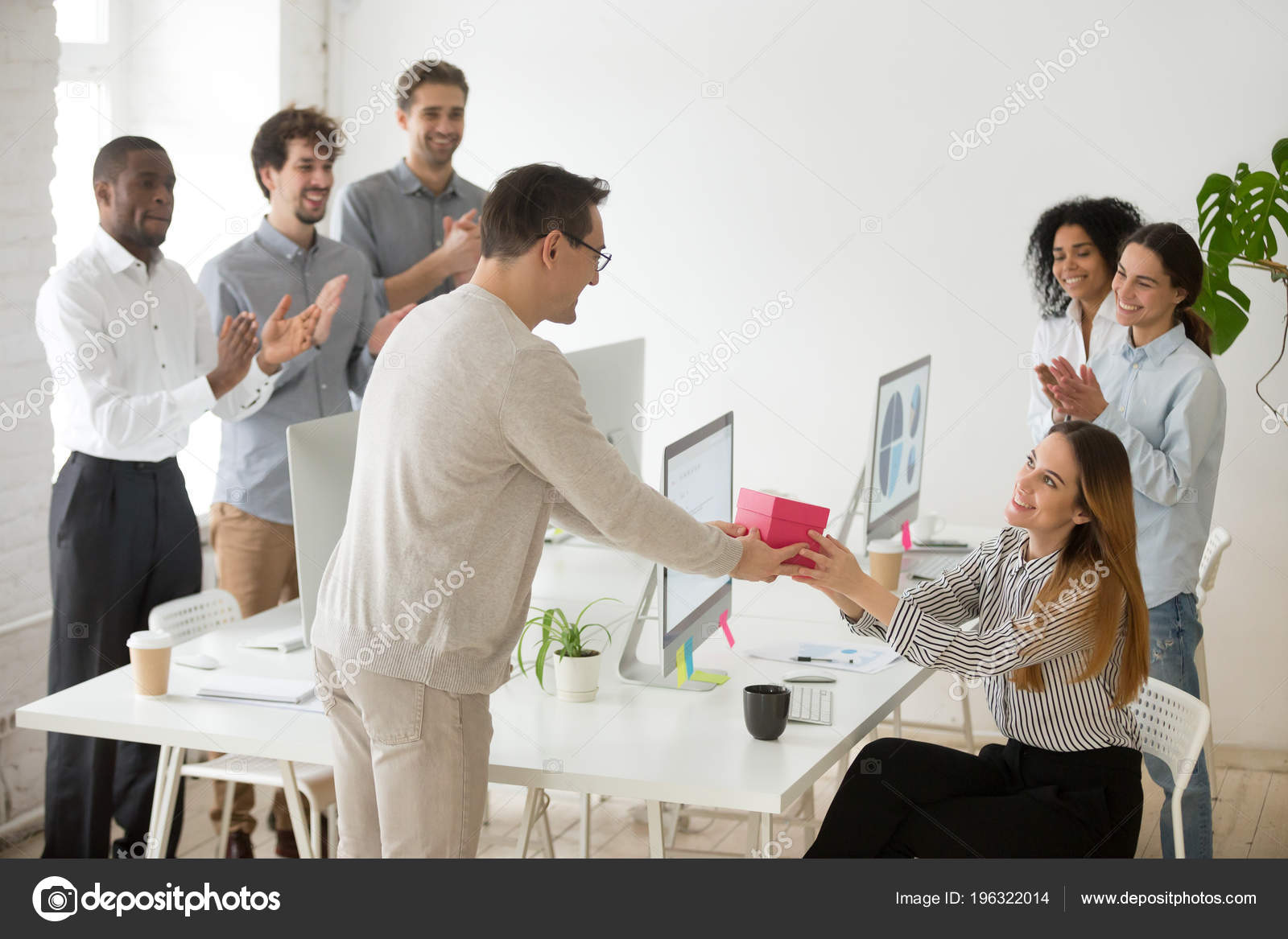 Friendly Team Congratulating Female Colleague With Birthday Gift Stock Photo