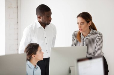 Serious multiracial team solving business problem together, diverse colleagues talking at workplace with computer, coworkers group discussing project focused on brainstorm or collaboration in office