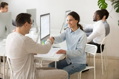 Smiling young woman handshaking satisfied client making deal in