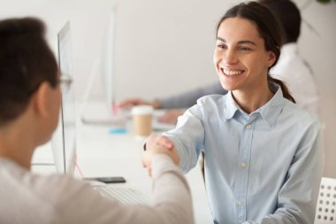 Happy hired intern, successful student, promoted woman employee smiling shaking boss hand congratulating worker for good work result, appreciating supporting young motivated professional by handshake