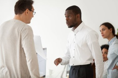 Diverse black employee and white boss arguing at work