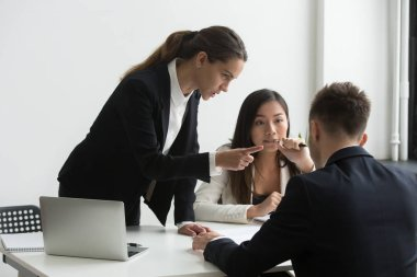 Dissatisfied female executive blaming threatening male employee
