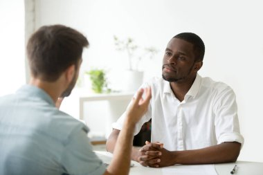 Friendly African American employer listening to work candidate d