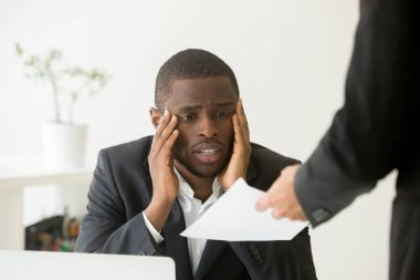 Upset African American worker getting dismissal notice