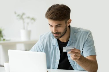 Happy man shopping online entering credit card information