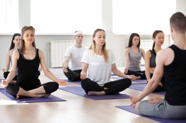 Group of sporty people doing Padmasana exercise with male instru