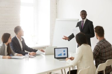 African American worker presenting in front of diverse colleague