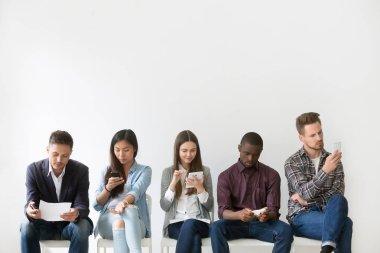 Multiethnic applicants preparing for job interview waiting in qu