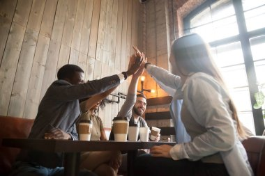 Happy diverse friends giving high five chilling out in cafe