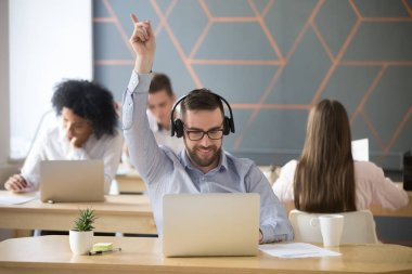 Excited male employee wearing headset dancing at workplace, working at laptop in coworking space, excited worker listening to music, relaxing during work break in office, man enjoying tracks at work