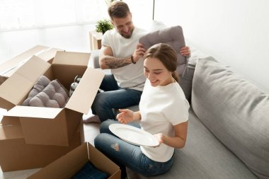 Homeowners unpacking boxes sitting on cozy sofa