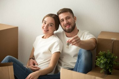 Portrait of couple holding keys excited to move in together
