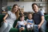 Portrét šťastný rodičů s roztomilé děti sedí na pohovce