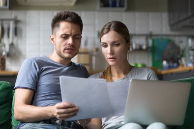 Serious confused couple checking domestic bills with papers and