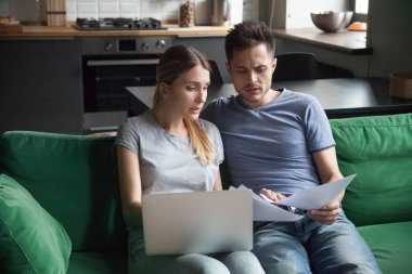 Worried couple reading documents or calculating high domestic bi