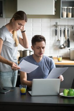 Confused young couple worried checking domestic bills having fin