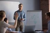 Fotografie Woman raising hand asking question during colleague presentation