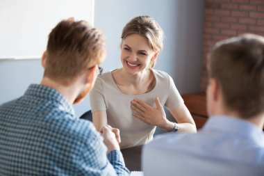 Male employer handshaking female colleague greeting with success