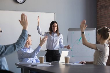 Employees raise hands taking part in teambuilding activity