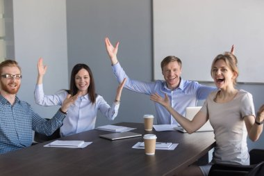 Portrait of excited colleagues raise hands up happy with success