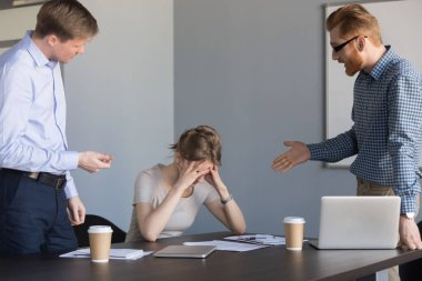 Angry businessmen shouting at female colleague blaming for failu