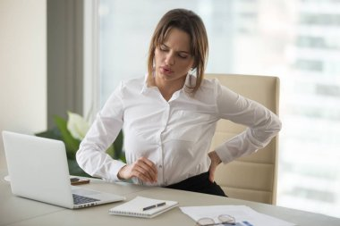 Upset businesswoman feeling back pain touching aching muscles in