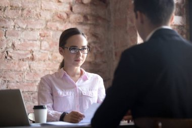 Serious young HR manager woman interviewing male candidate