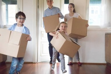 Excited kids running carrying boxes moving to new house