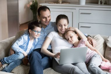Happy family with kids enjoy watching cartoons at laptop togethe