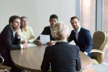 Woman passing job interview at office, interviewers on backgroun
