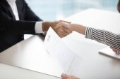 Photo Close up of HR manager handshaking male applicant at interview