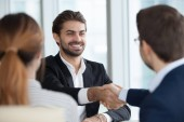 Photo Happy male employee handshaking HR managers after good interview