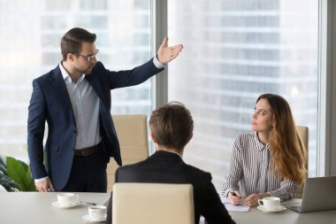 Mad male worker asking female partner leave meeting