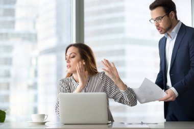 Bothered businesswoman rejecting accept document from colleague