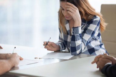 Serious wife signing divorce decree in lawyer office