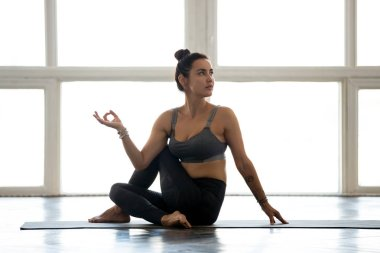 Young sporty attractive woman practicing yoga, doing Revolved Ea