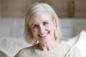 Šťastný střední věku starší šedé vlasy žena při pohledu na fotoaparát