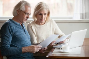 Serious worried senior couple reading documents calculating bill