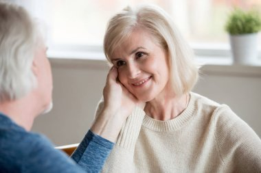 Caring senior husband touching beautiful face of smiling aged wi