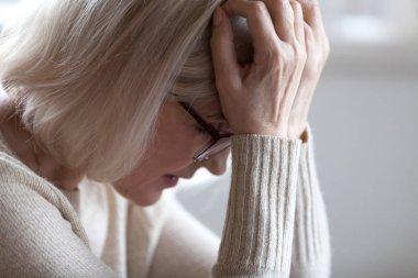 Sad tired senior woman holding head in hands feeling headache