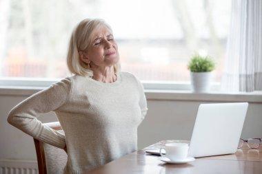 Upset mature woman sitting feeling back pain massaging aching mu