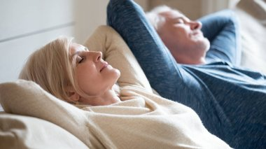 Senior aged couple relaxing on comfortable sofa together breathi