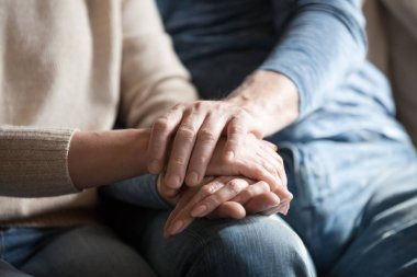 Closeup view of mature couple holding hands giving psychological