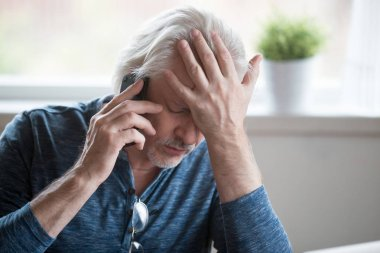 Frustrated mature man feeling upset desperate talking on the pho