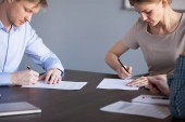 Fotografie Businessman and businesswoman put signatures on paper contracts