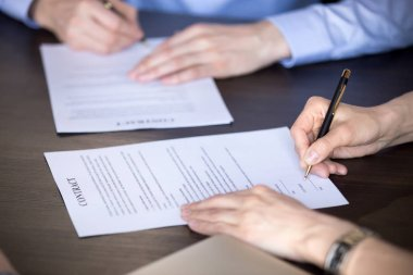 Close up of male and female hands signing two contracts