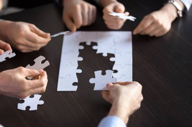 Business team connecting puzzle together finding solution, close
