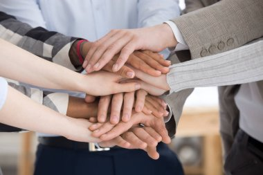 Close up group of people stacking hands