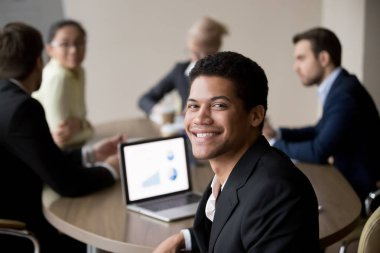 Portrait of smiling African American employee posing at meeting